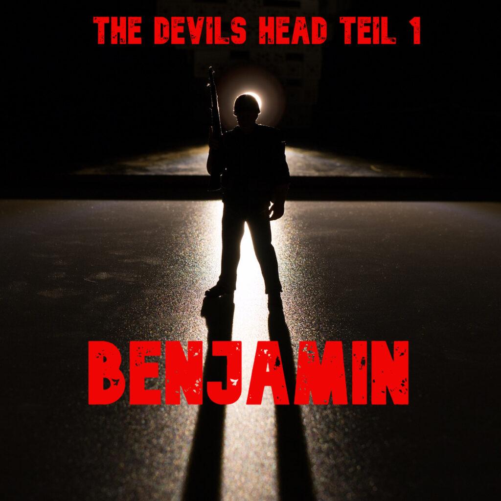 Man sieht die Silhouette eines behelmten Soldaten auf einer schimmernden grauen Fläche stehen.  Er wird von hinten beleuchtet und diffuses Licht umgibt ihn. In der rechten Hand hält er ein Gewehr waagerecht nach oben.  Darüber steht in roter Schrift: The Devils Head teil eins.  Darunter etwas dicker in er selben Farbe: Benjamin