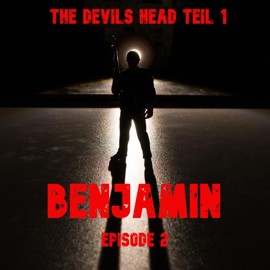 Man sieht die Silhouette eines behelmten Soldaten auf einer schimmernden grauen Fläche stehen.  Er wird von hinten beleuchtet und diffuses Licht umgibt ihn. In der rechten Hand hält er ein Gewehr waagerecht nach oben.  Darüber steht in roter Schrift: The Devils Head teil eins.  Darunter etwas dicker in er selben Farbe: Benjamin Episode 2